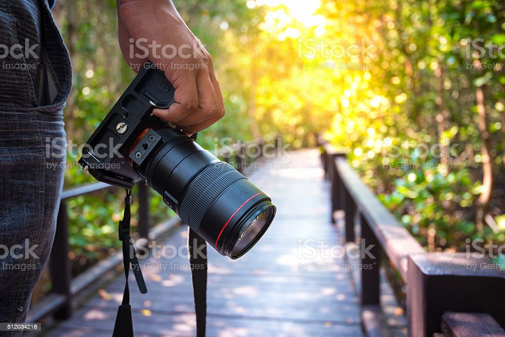 Man holding his camera on walkway during his travel stock photo