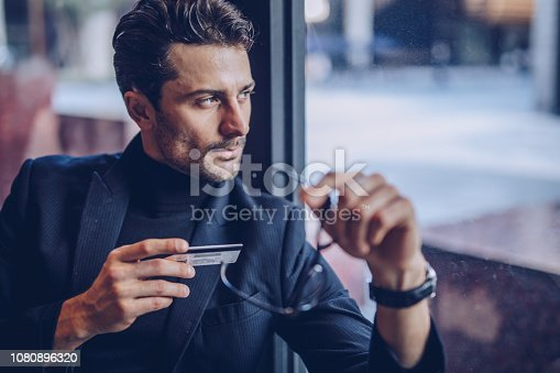 istock Man holding his credit card 1080896320