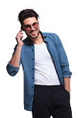 Handsome casual man holding his hand in pocket while talking on the phone, smiling for the camera.
