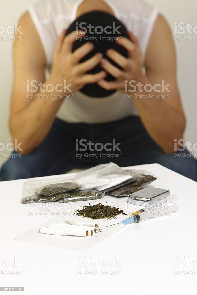 A man holding his head in his hands over drug addiction stock photo