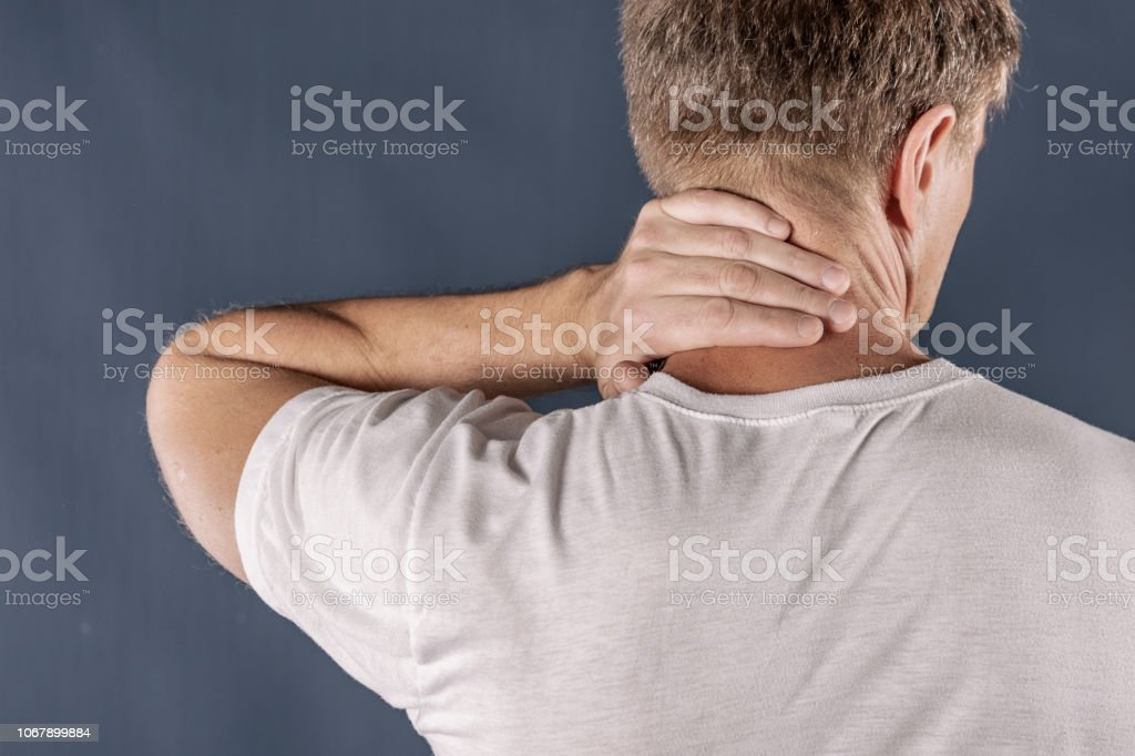 Man holding his neck trying to relieve pain