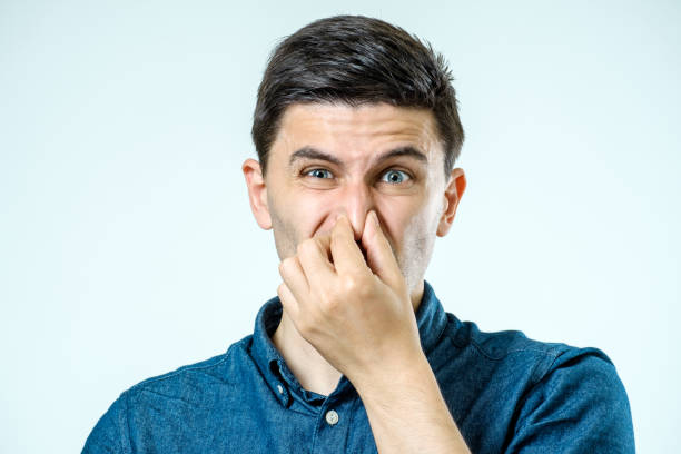 Man holding his nose against a bad smell over gray background stock photo