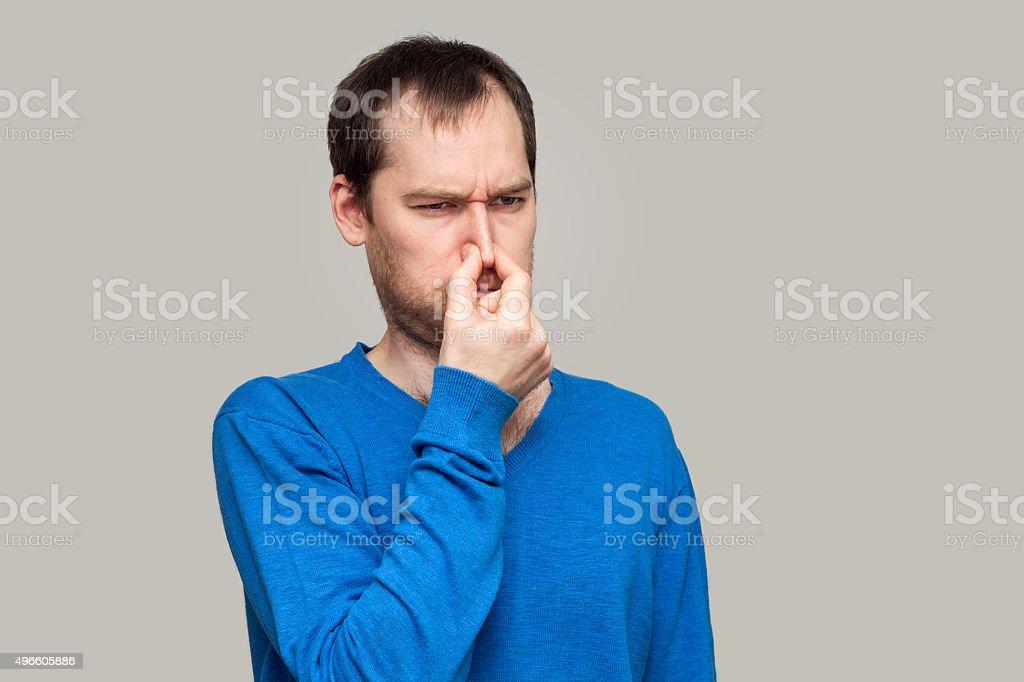 Mann hält seine Nase wegen einer schlechten Geruch – Foto