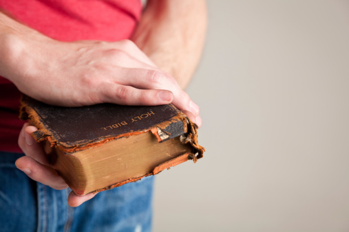 Man holding his old used bible