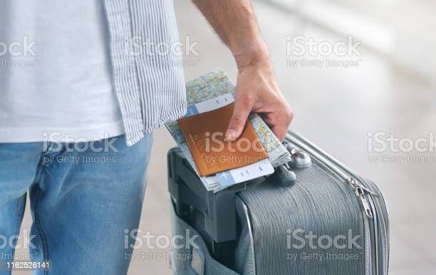 Man holding his passport and carrying suitcase close up picture id1162526141?b=1&k=6&m=1162526141&s=612x612&h=dj8dlgcztinrcdtcib 9rbefwhqkkfk xgma7sijxve=