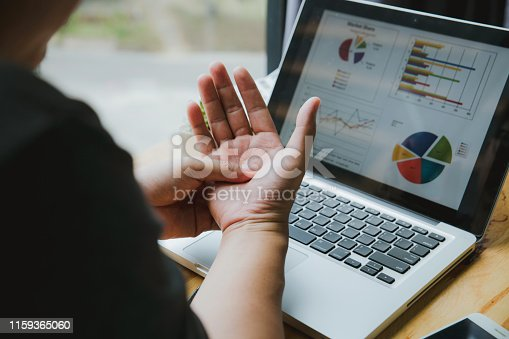Man holding his wrist close-up . Pain from using computer. Office syndrome hand pain by occupational disease.
