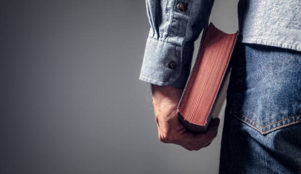 Man holding holy bible with gray background for text stock photo