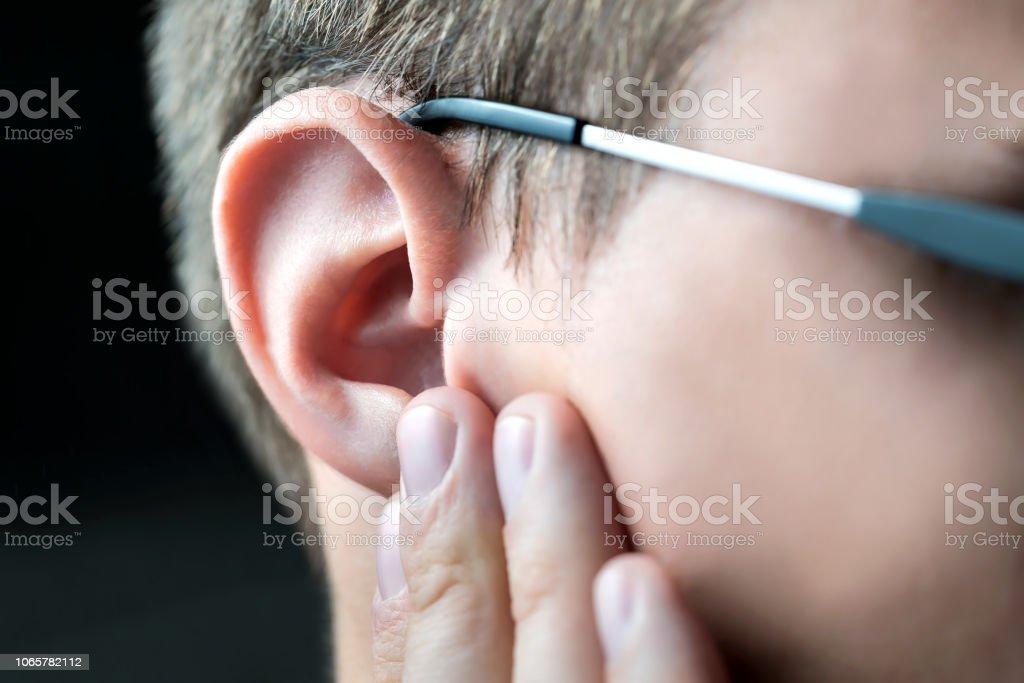 Mann, der schmerzende Ohr mit der Hand hält. Ohrenschmerzen und Schmerzen. Otitis oder Infektion im Gehörgang. Hör- oder Verlust. Jungen Menschen mit Tinnitus. Leiden unter Juckreiz Ohrenschmalz. - Lizenzfrei Ansteckende Krankheit Stock-Foto