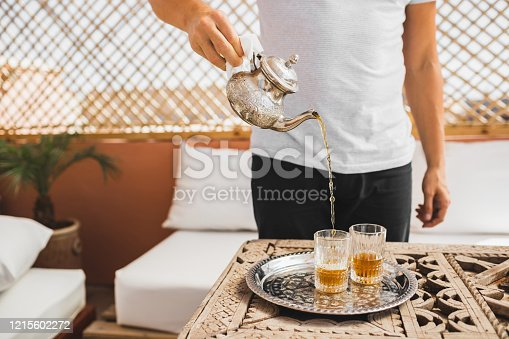 Man holding in hand silver vintage teapot and pouring traditional mint sweet moroccan tea. Arabian hospitality and service.