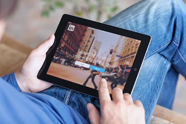 man holding ipad with app linkedin on the screen - linkedin bildbanksfoton och bilder