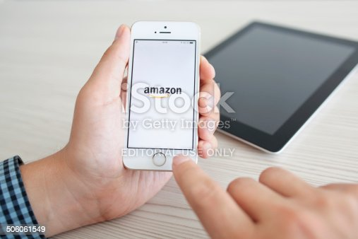 istock man holding iPhone 5s with app Amazon on the screen 506061549