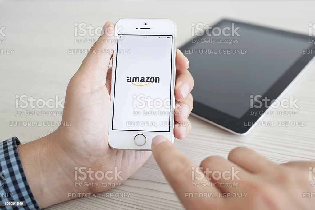 man holding iPhone 5s with app Amazon on the screen stock photo