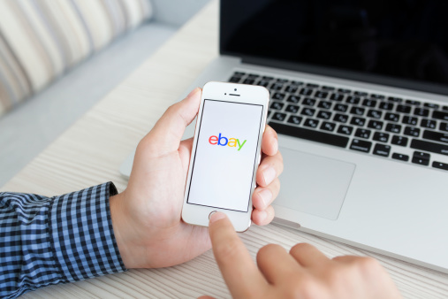 man holding iPhone 5s with app eBay on the screen