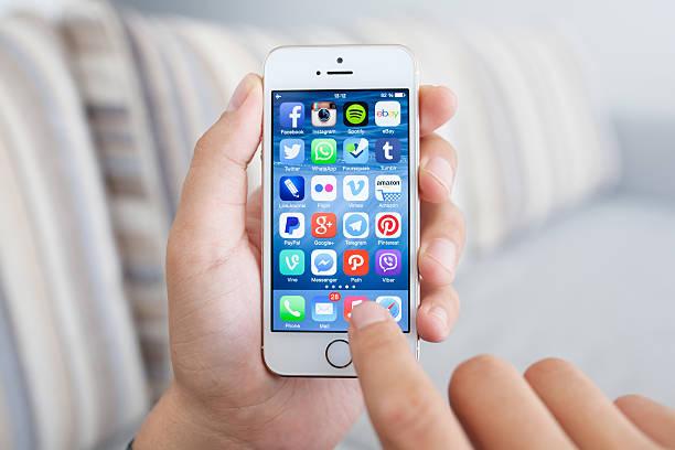 uomo tenendo iphone 5s con programma di rete di social media - paypal foto e immagini stock