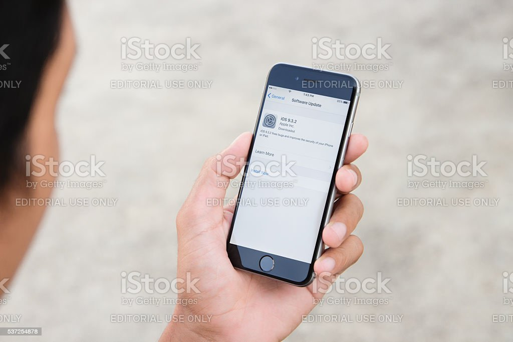 Man holding iphone 6 ios software system new version update stock photo