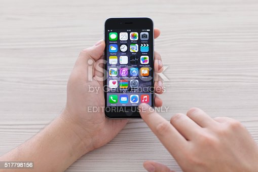 istock man holding iPhone 6 Space Gray over the table 517798156