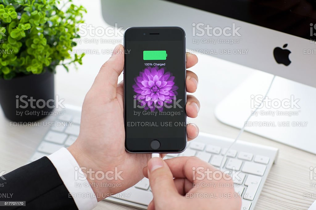 Man holding iPhone 6 Space Gray with battery icon stock photo