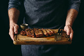 istock Man holding juicy grilled beef steak with spices on cutting board 930713290