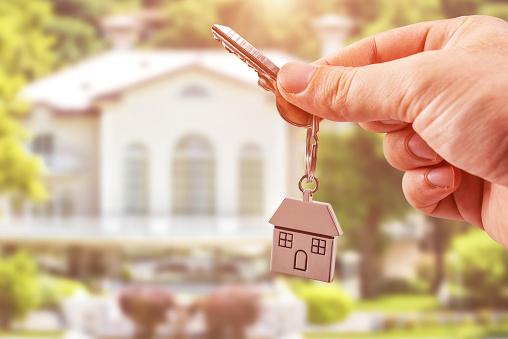 istock Man Holding keys on house shaped keychain 665341436