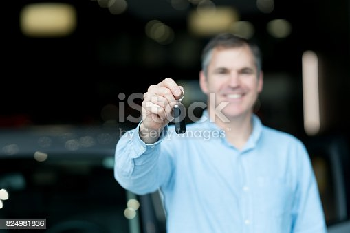 1138561232 istock photo Man holding keys to a car at the dealership 824981836