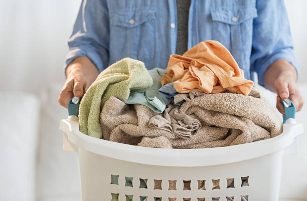 Man Holding Laundry Basket At Home Midsection of mature man holding laundry basket at home laundry basket stock pictures, royalty-free photos & images