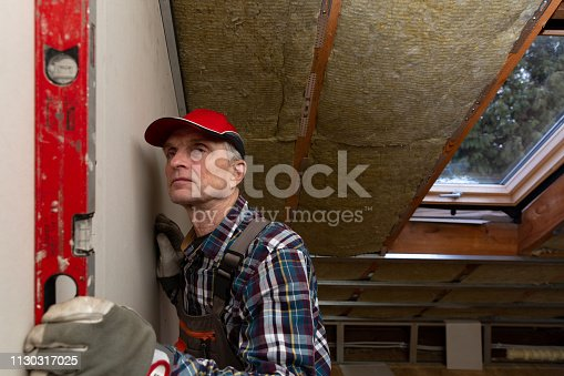 466705128 istock photo Man holding level against interior drywall. Attic insulation and renovation 1130317025