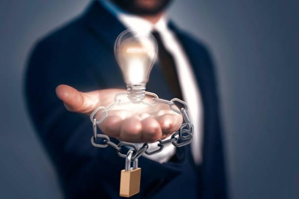 un homme retenant l'ampoule, la serrure et la chaîne. concept d'idée breveté. tous droits réservés - marque déposée photos et images de collection