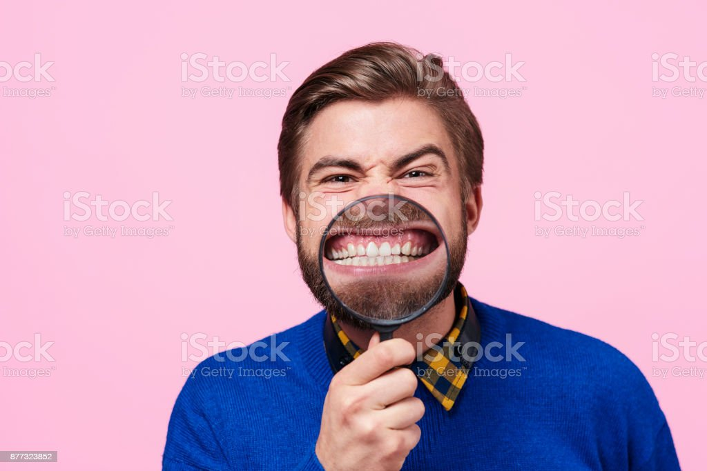Man holding magnifying glass against open mouth stock photo
