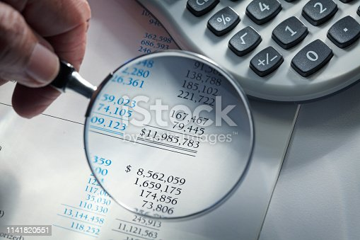 Close up of a man holding a magnifying glass over a financial report.  A calculator sits off to the side.