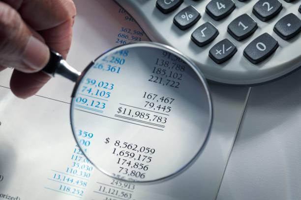Man hält Glas über Finanzbericht – Foto