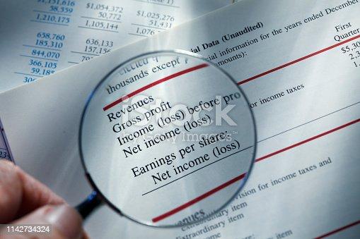 Close up of a man holding a magnifying glass over a financial report that states a company's revenues and profits.