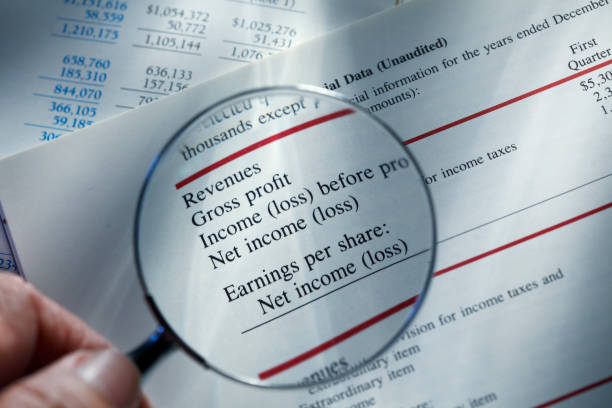 Man Holding Magnifying Glass Over Financial Report Close up of a man holding a magnifying glass over a financial report that states a company's revenues and profits. bank statement stock pictures, royalty-free photos & images