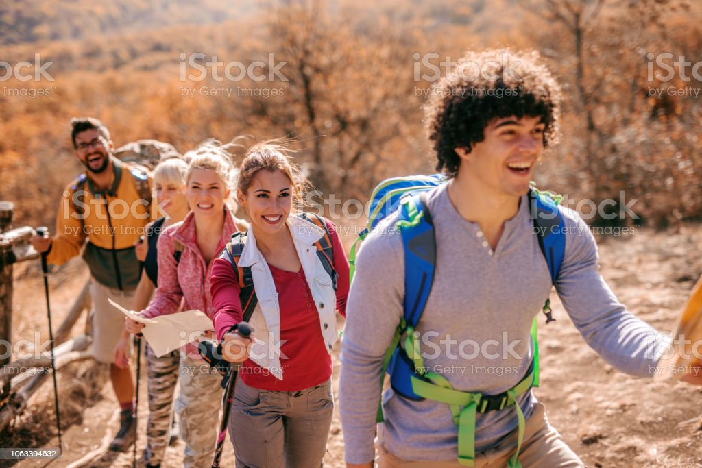 Man holding map and leading small group of hikers. Autumn season,...