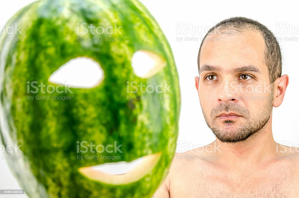 man holding mask of fruit or watermelon over his face stock photo