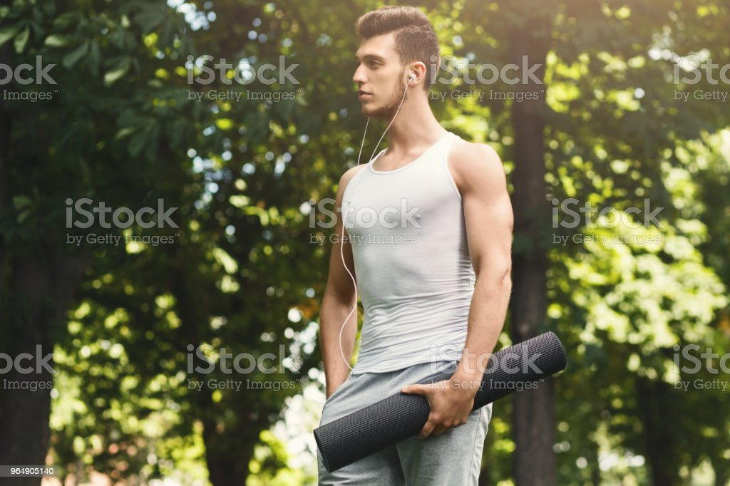 Man holding mat and listening to music in park royalty-free stock photo