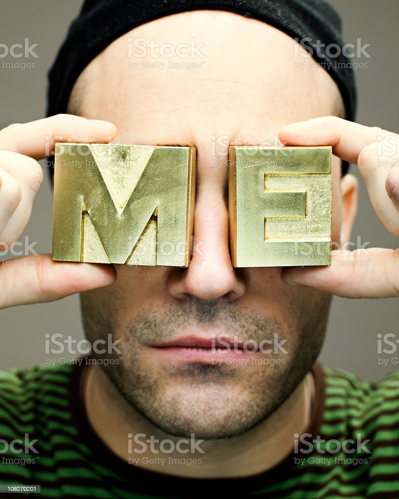 man holding 'me' block letters to face royalty-free stock photo