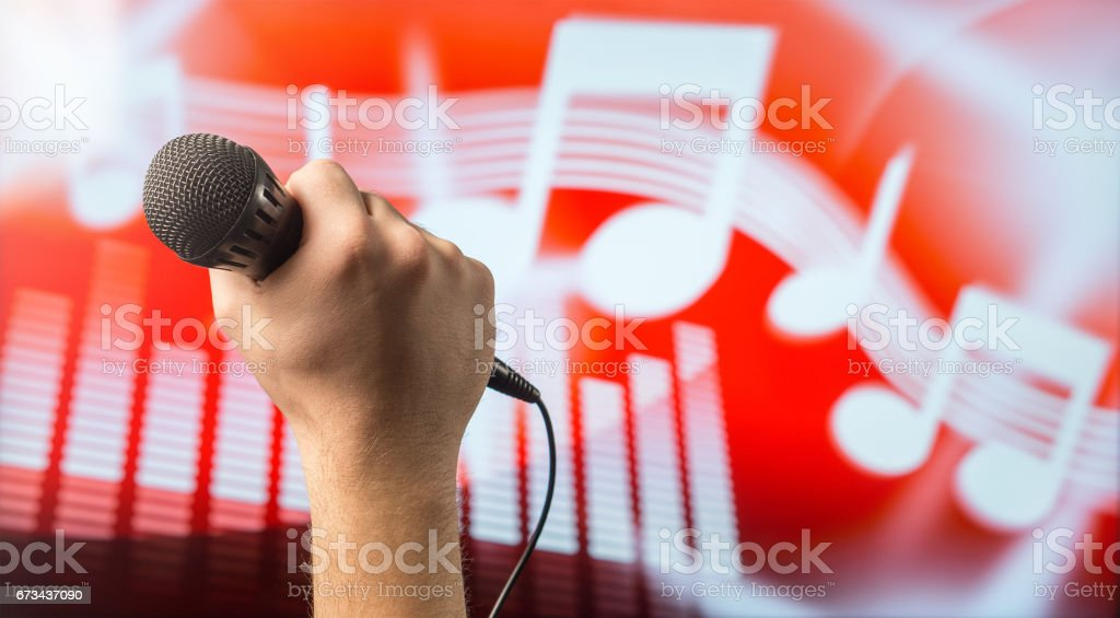 Man holding microphone in front of an abstract music and note background. Karaoke or singing contest theme. Vocal coaching or live singing concept with copy space for text. stock photo
