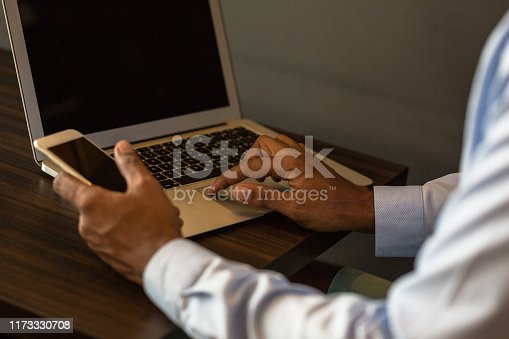 650662058istockphoto Man holding mobile phone and using laptop 1173330708