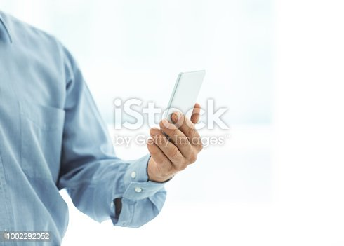 istock man holding mobile phone 1002292052