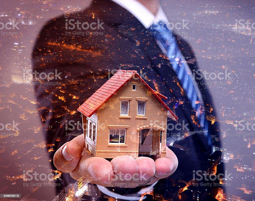 Man holding model house double exposure stock photo