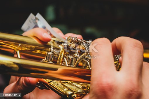 Detail of hands of a man playing on the trumpet while holding a euro note money bill. Concept of earning money with playing music with a band on different ocasions