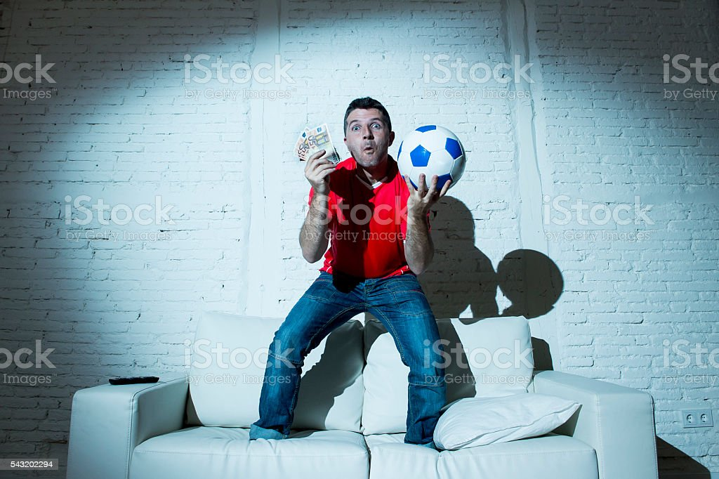 man holding money and soccer ball nternet online bet gambling stock photo