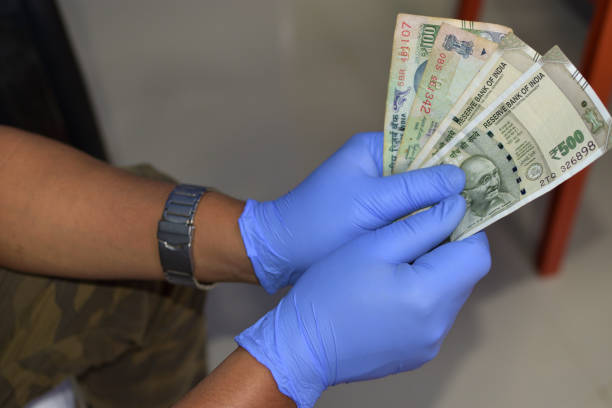 Man holding money indian rupees in hand in black medical gloves. Coronavirus crisis. Save money. Man holding money indian rupees in hand in black medical gloves. Coronavirus crisis. Save money. selective focus. depreciation stock pictures, royalty-free photos & images