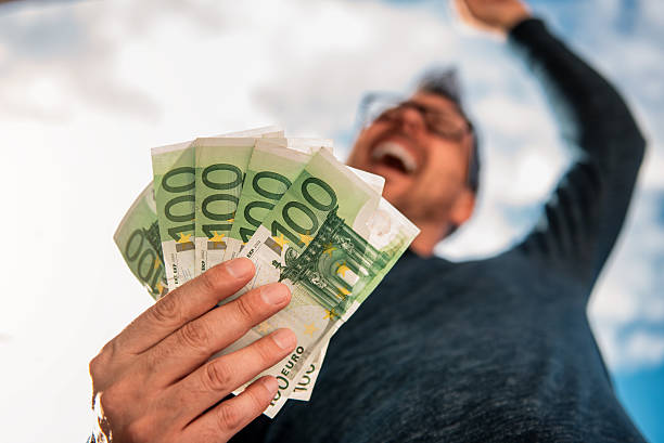 Man Holding Money Man with glasses wearing blue shirt. and holding stack of money. euro symbol stock pictures, royalty-free photos & images