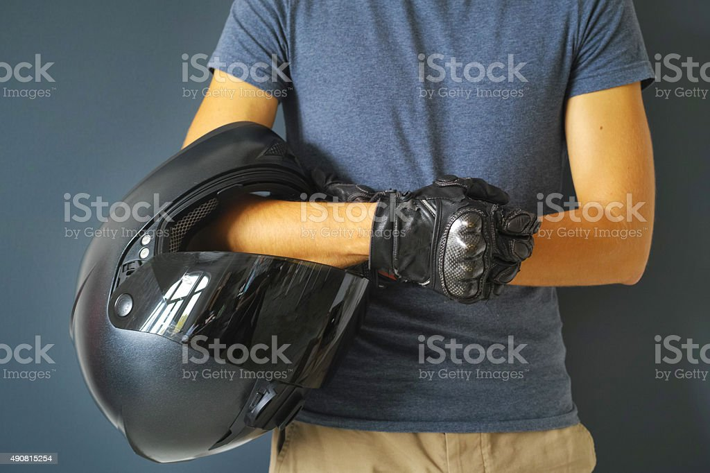 Man Holding Motorcycle Helmet On Arm With Hands In Gloves stock photo