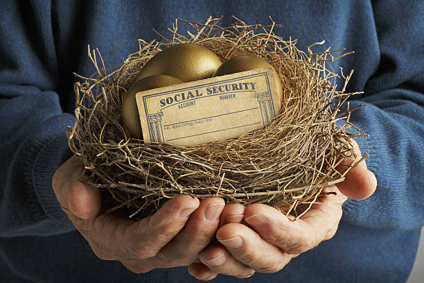 Man Holding Nest With Golden Eggs And Social Security Card A senior male holds a nest that contains two golden eggs and a  blank social security card.  He holds the nest close to his chest in front of a blue sweater he is wearing. social security stock pictures, royalty-free photos & images
