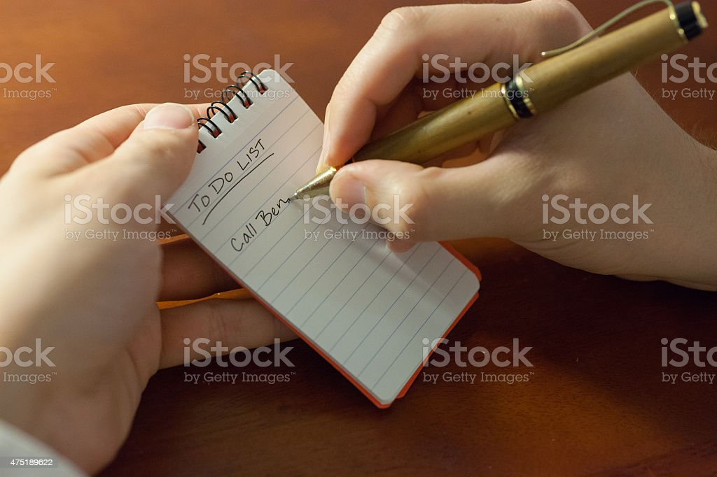 Man holding note pad and pen writing stock photo