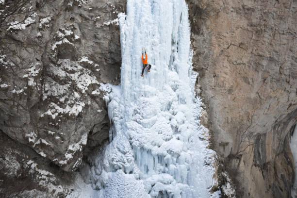 man holding on ice axes while climbing on frozen waterfall - アイスクライミング ストックフォトと画像