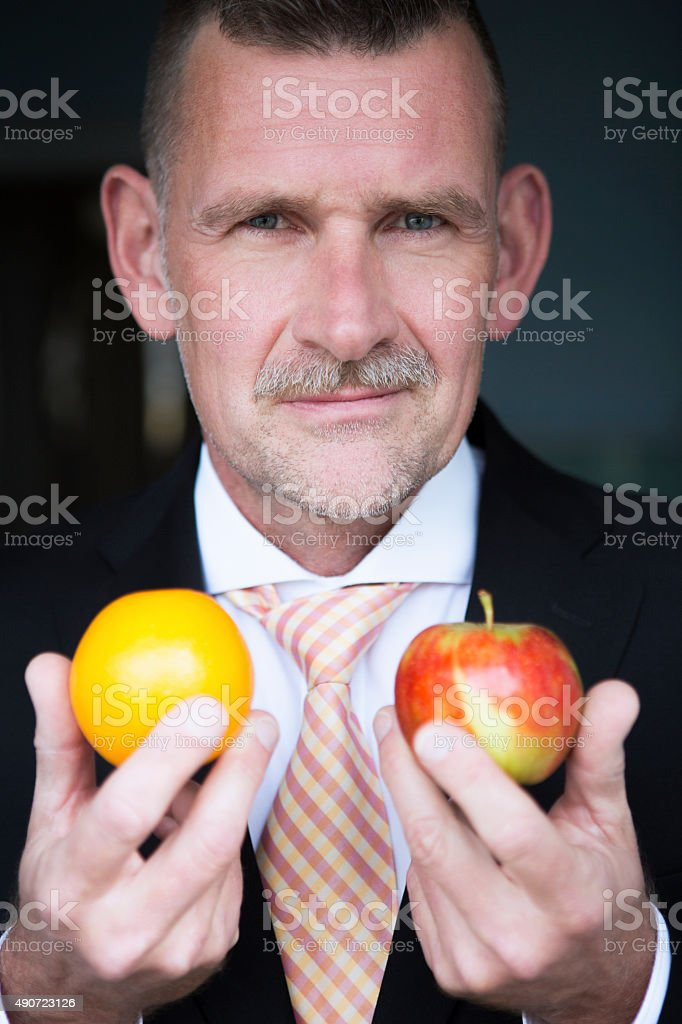 man holding orange and apple in his hands stock photo
