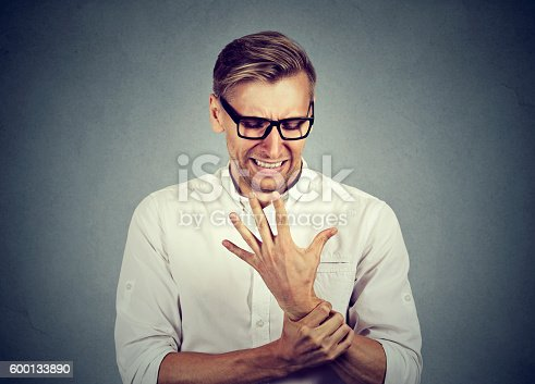 668285874istockphoto man holding painful wrist arm. Sprain pain 600133890